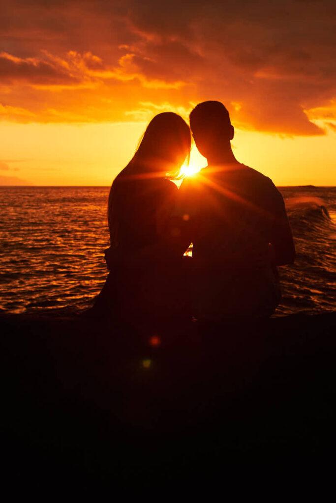 Paar genießt zusammen mit Ela & Chris Fotograf Teneriffa den Sonnenuntergang am Strand auf den Felsen