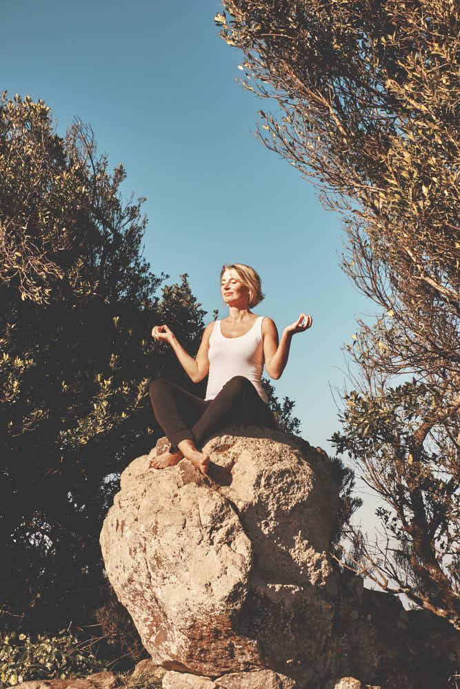 Business Kundin und Life Coach Trainerin sitzt auf Fels in der Sonne beim Fotoshooting und Shooting mit Fotograf Teneriffa