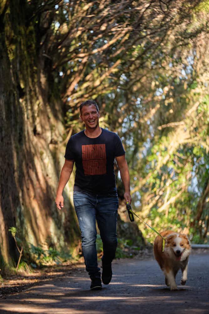 Business Coach läuft mit seinem Hund beim Fotoshooting auf Teneriffa durch das Anaga Gebirge