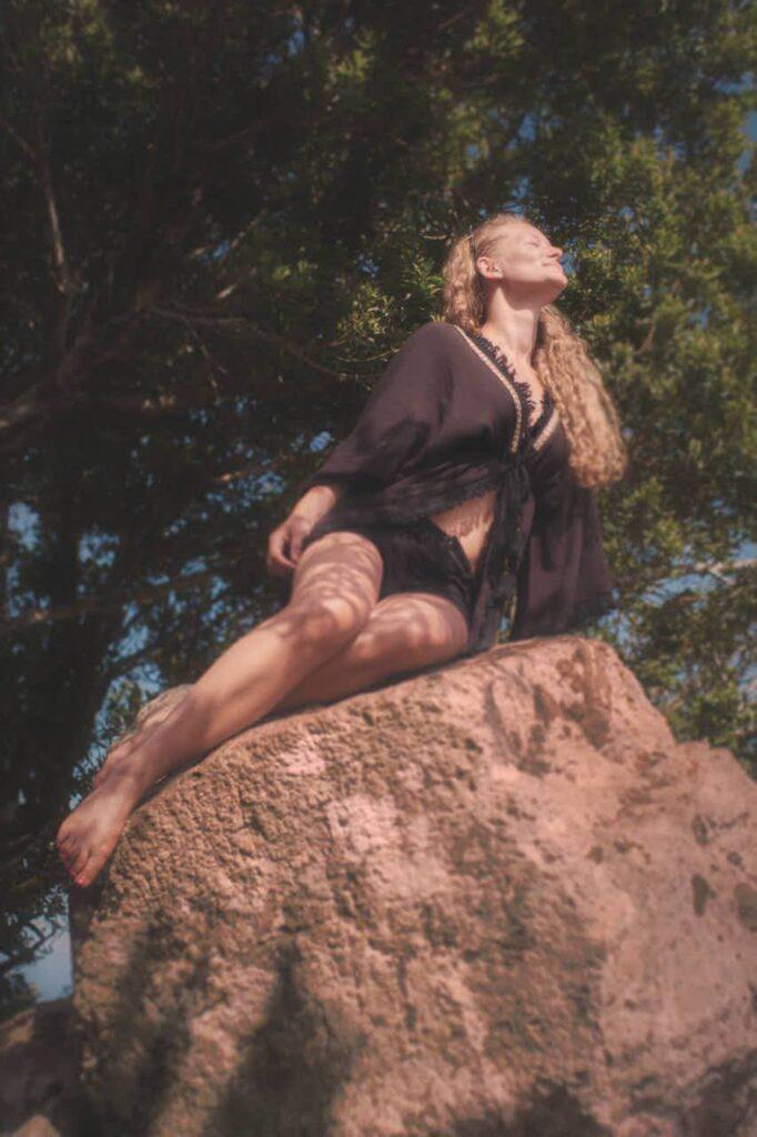 Mädchen genießt barfuß auf einem Felsen sitzend bauchfrei die Sonne beim Fotoshooting mit Deutscher Fotograf Teneriffa