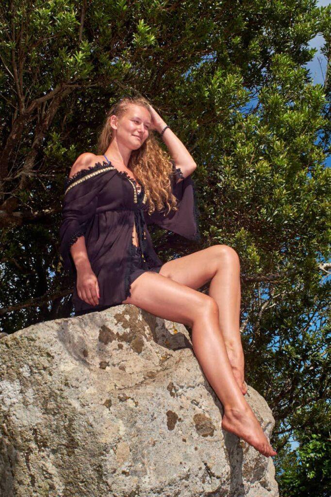 Hübsches Mädchen sitzt barfuß auf einem Fels im Anagagebirge beim Shooting mit Fotograf Ela & Chris