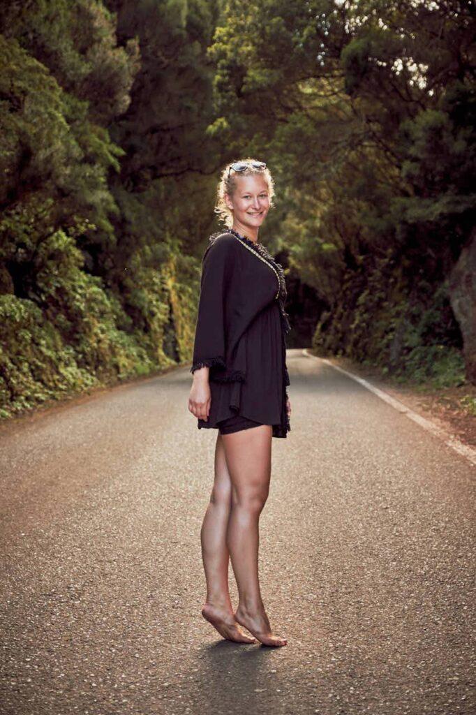 Barfüssig steht ein Mädchen auf einer Strasse im Anagagebirge auf Teneriffa für die Fotografen Ela & Chris Modell
